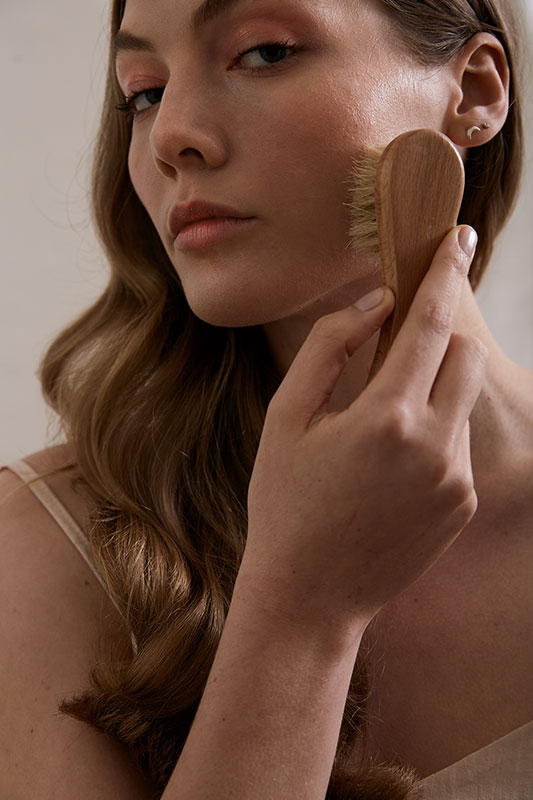 woman using facial brush